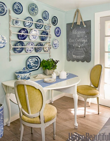 blue willow wall hanging plates with yellow chairs via house beautiful