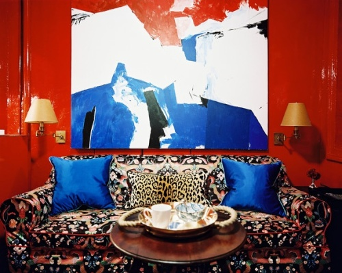 black floral couch with red lacquer walls
